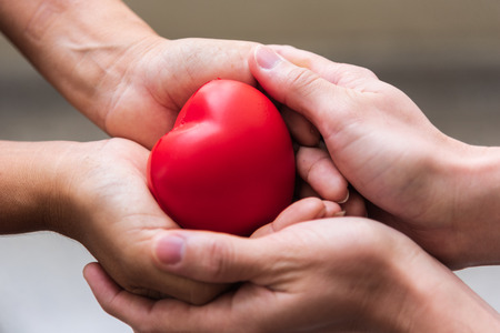 Close up hand giving red heart as heart donor. Valentine day of love concept. Medical ventilator and heart donator charity. Sign of compassion and healthy. Helping doctor hand in freedom life donation