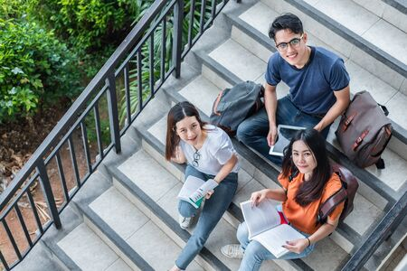 Three Asian young campus students enjoy tutoring and reading books together at library stair. Friendship and Education concept. Campus school and university. Happiness and fun of learning in college. Imagens