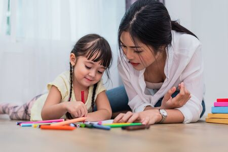 Mom teaching her daughter to drawing in art class. Back to school and Education concept. Children and kids theme. Home sweet home theme.