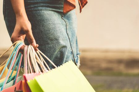 Closeup of woman holding color paper shopping bag at street. Summer sale and Black Friday shopping concept. Vintage tone film in cover size photo.