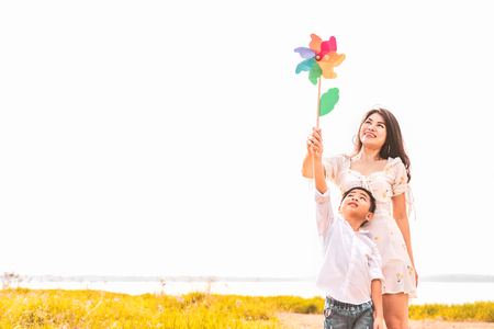 Little Asian boy and his mom playing colorful rainbow turbine in meadow. Mother and son playing together. Celebrating in Mother day and appreciating concept. Summer people and lifestyle theme.