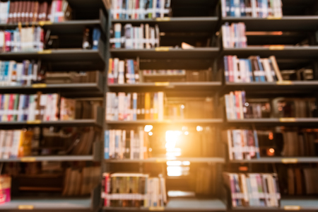 Blurry background of library in college with sun light. Abstract and Self education learning concept.