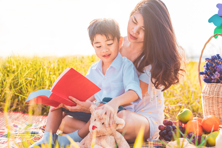 Little Asian boy and his mother reading books when doing picnic in meadow. Mother and son learning together. Celebrating in Mother day and appreciating concept. Summer people and lifestyle education