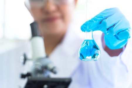 Female scientist hold and showing laboratory test tubes and solution with stethoscope. Science and Medical background. Scientist research and analysis biotechnology concept. Selective focus blue flask
