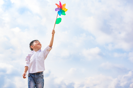 Boy holding colorful pinwheel in windy at outdoors. Children portrait and kids playing theme.