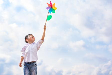 Ragazzo che tiene la girandola colorata in ventoso all'aperto. Ritratto di bambini e bambini che giocano a tema.