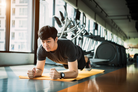 Portrait of Asian fitness man doing planking exercise in gym. People lifestyle and Sport workouts concept.