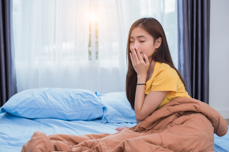 Asian woman getting up in morning in lazy posture in bedroom at home. People lifestyles and Health care concept. Overnight sleeping theme. Stock Photo