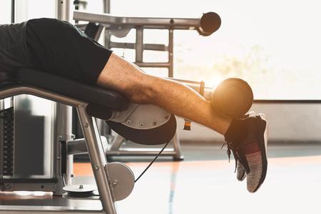 Nahaufnahme des Sportlers, der Gewicht mit zwei Beinen streckt und hebt, wenn er nach unten zeigt, um Muskeln im Fitnessstudio im Hintergrund der Eigentumswohnung zu dehnen. Sport- und Menschenlebensstilkonzept. Standard-Bild