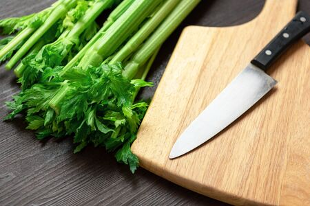 Bunch of fresh celery stalk on wooden table and cutting board and knife with leaves. Food and ingredients  of healthy vegetable. Freshness herbal and low calories for dieting with plenty of vitamin