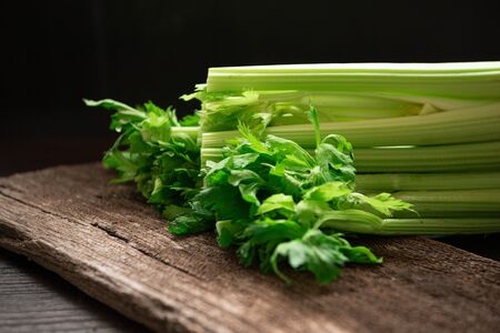 Bunch of fresh celery stalk on wooden table with leaves on black background. Food and ingredients  of healthy vegetable. Freshness herbal and low calories for dieting with plenty of vitamin