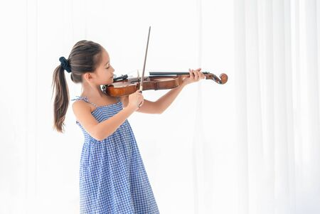 Cute girl playing violin in white bedroom with white curtain background. Musical and people lifestyles. Education and recreation concept. Back to school theme