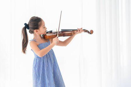 Nettes Mädchen, das Violine im weißen Schlafzimmer mit weißem Vorhanghintergrund spielt. Musik- und People-Lifestyle. Bildungs- und Erholungskonzept. Zurück zum Schulthema Standard-Bild