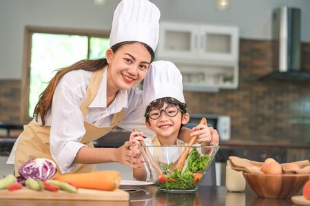 Beautiful Asian woman and cute little boy with eyeglasses prepare to cooking in kitchen at home. People lifestyles and Family. Homemade food and ingredients concept. Two Thai people looking at camera 写真素材