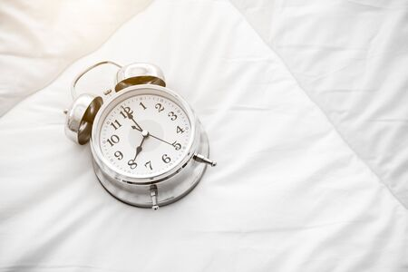 Ringing alarm clock on white bed sheet. Top view of object. 8 o clock setting up Imagens