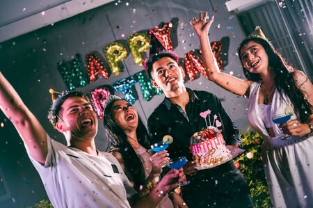 Asian friends having fun in birthday party at night club with birthday cake. Event and anniversary concept. People lifestyles and friendship. Imagens