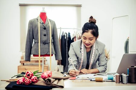 Attractive Asian female fashion designer  working in home office workshop. Stylish fashionista woman creating new cloth design collection. Tailor and sewing. People lifestyle and occupation concept Imagens