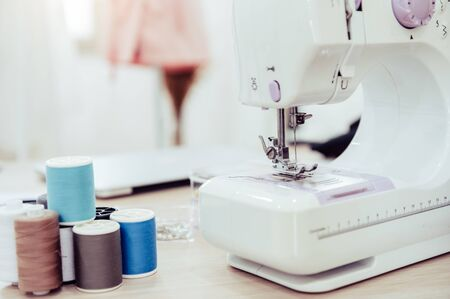 Nahaufnahme der Nähmaschine mit Modedesigner-Showroom-Studio-Workshop-Hintergrund mit neuer Kollektion rosafarbener pastellfarbener weiblicher Kleidung. Schneider- und Nähkonzept. Schneiderin moderne Zimmereinrichtung