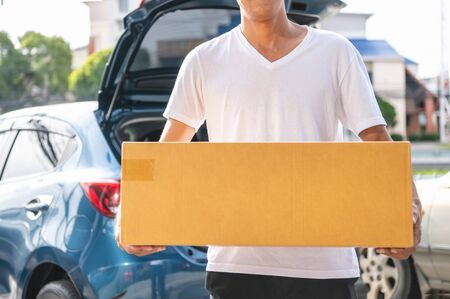 Closeup of happy Asian man delivering cardboard box to customers via private car. People lifestyles and business occupation concept. Young male courier in casual clothes. Shipping and packaging