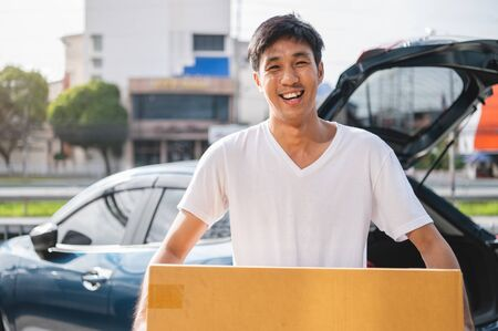Happy Asian man is delivering cardboard box to customers via private car. People lifestyles and business occupation concept. Young male courier in casual clothes