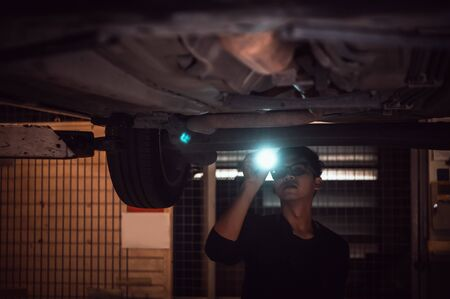 Lonely Asian male shining flashlight to examine car under chassis of automotive vehicle at old abandoned garage in night scene. Haunted and horror. Fantasy and mystery concept. Halloween theme.
