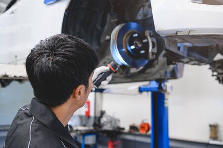 Asian male mechanical hold and shining flashlight to examine car disk brake pad wear of automotive vehicle. Safety suspension inspection check service maintenance for customer before road trip concept