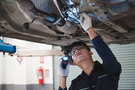 Asian male mechanical hold and shining flashlight to examine car under chassis of automotive vehicle. Safety suspension inspection check service maintenance for customer before road trip concept