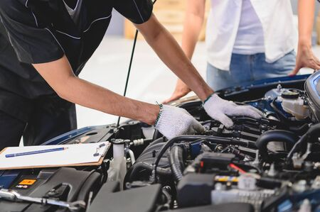 Asian male auto mechanic examine car engine breakdown problem in front of automotive vehicle car hood with female customer. Safety technical inspection care check service maintenance for road trip