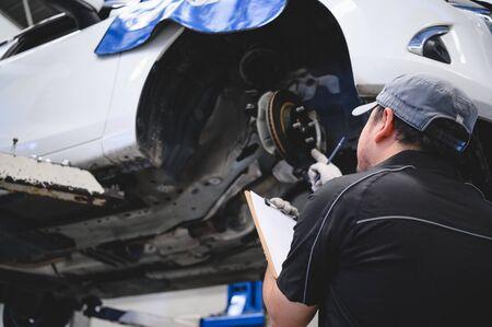 Aziatische mannelijke autotechnicus auto-onderhoud voor klanten volgens de gespecificeerde checklist voor voertuigonderhoud. Schijfremblok slijtage auto reparatie op voertuig. Veiligheidsinspectie check service