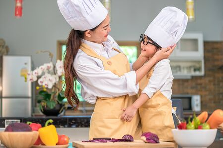 Happy cute little boy with eyeglasses looking beautiful Asian woman mother each other while prepare to cooking in kitchen at home. People lifestyles and Family. Homemade food and ingredients concept.