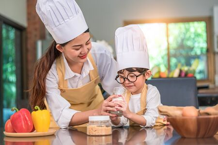 Beautiful Asian woman teaching cute little boy with eyeglasses to drink milk in kitchen at home together. Lifestyles and Family. Son dislike milk and doing funny face with milk glass. Food and drink Imagens