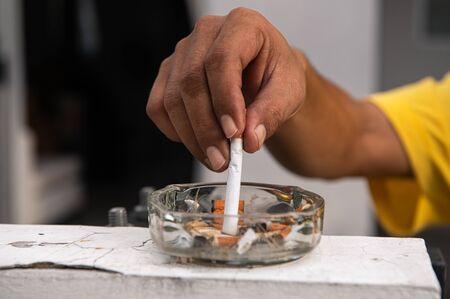 Hand, die Zigarette ausstellt und im Aschenbecher im Freien vor dem Haus zerstört. Gesundes und Menschenkonzept. Thema Weltnichtrauchertag
