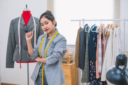 Fashion designer stylist in business owner workshop. Tailor and sewing concept. Portrait of happy casual trendy fashion designer businesswoman in studio looking camera. Business job and occupation