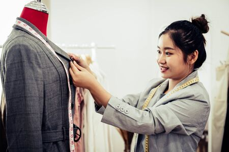 Asian female fashion designer girl making fit on the formal suit uniform clothes on mannequin model. Fashion designer stylish showroom. Sewing and tailor concept. Creative dressmaker stylist.