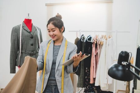 Fashion designer stylist in business owner workshop with tablet and customer contact list. Tailor and sew concept. Portrait of happy casual trendy fashion businesswoman in studio. Job and occupation