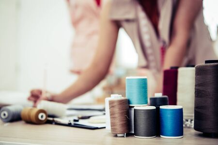 Closeup of colorful thread with fashion designer background in workshop studio. Stylish fashionista woman creating new cloth design collection. Tailoring and sewing People lifestyle and occupation