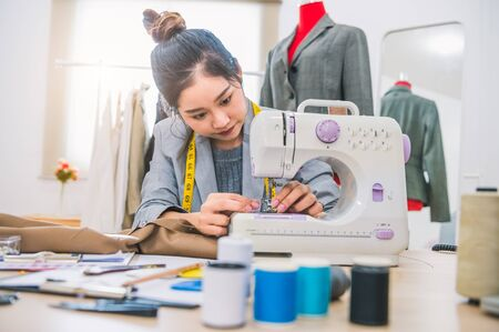 Attractive female fashion designer hand working in workshop with sewing machine. Stylish fashionista woman creating new cloth design collection. Tailoring and sewing Lifestyle and business occupation