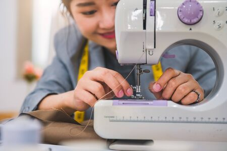 Closeup of attractive female fashion designer hand working workshop with sewing machine. Stylish fashionista woman creating new cloth design collection. Tailoring and sewing Lifestyle and occupation