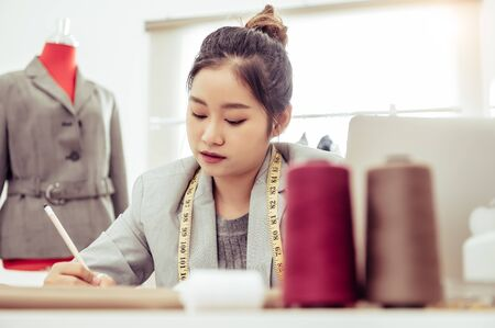 Attractive Asian female fashion designer working in home office workshop. Stylish fashionista woman creating new cloth design collection. Tailor and sewing. People lifestyle and occupation concept
