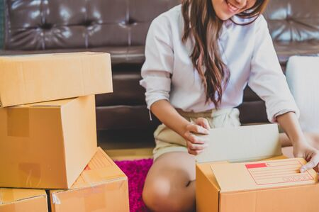 Asian business woman startup small business entrepreneur SME distribution warehouse with parcel mail box. small owner home office. Online marketing and product packaging and delivery service concept