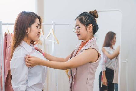 Dressmaker measuring female customer shoulder and chest in sewing atelier workshop office. Tailor and fashion designer concept. Job and freelance occupation. Business people in clothing shop Stock fotó