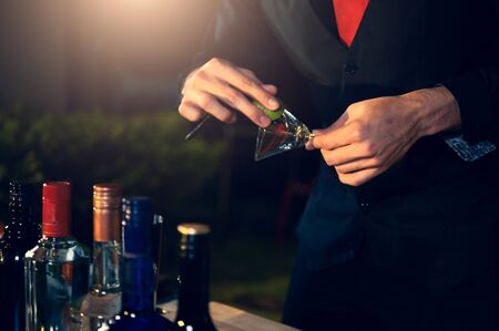 Professional bartender preparing fresh lime lemonade cocktail in drinking wine glass with ice at night bar clubbing counter. Occupation and people lifestyles concept. Outdoor background