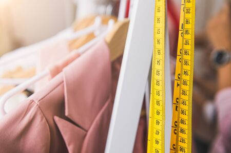 Closeup of measuring tape and line of fashion pastel pink colored woman shirts with wooden hangers in clothing shop.