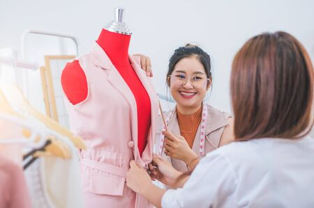 Attractive Asian female fashion designer working and recommending new design collection clothes on mannequin in clothing shop to customer. Tailor and sewing dressmaker. People lifestyle concept
