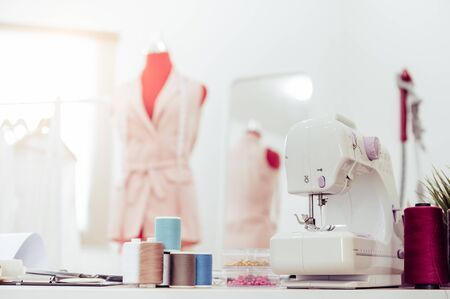 Closeup of sewing machine with fashion designer showroom studio workshop background with new collection of pink pastel female clothes design. Tailor and sewing concept. Dressmaker modern room interior Banco de Imagens