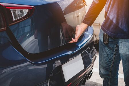 Closeup of man hand opening hatchback trunk by touching sensor door. People lifestyle and transportation technology. Travel and road trip concept. Automotive transportation and outdoors theme Banco de Imagens