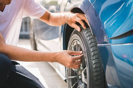 Closeup male automotive technician removing tire valve nitrogen cap for tire inflation service at garage or gas station. Car annual maintenance and repair concept. Safety road trip and travel theme. Stok Fotoğraf