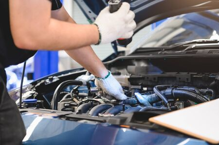 Asian male mechanic hold and shining flashlight to examine car engine problem in front of automotive vehicle car hood. Safety inspection check service maintenance for customer before long road trip