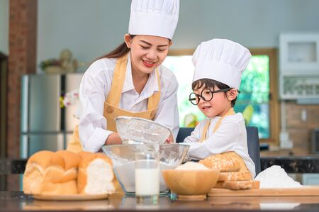 Cute little Asian boy and beautiful mother sifting dough flour with sifter sieve colander in home kitchen on table for prepare to baking bakery and cake. Thai kids playing with flour as chef funny