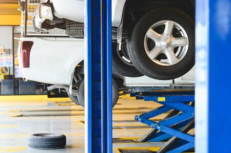 Pickup car raised on car lift in auto service garage center for tire change. Automotive car repairing and maintenance concept. Stock Photo